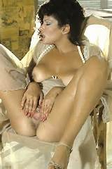 Vanessa Del Rio enjoys her body laying on the bed: